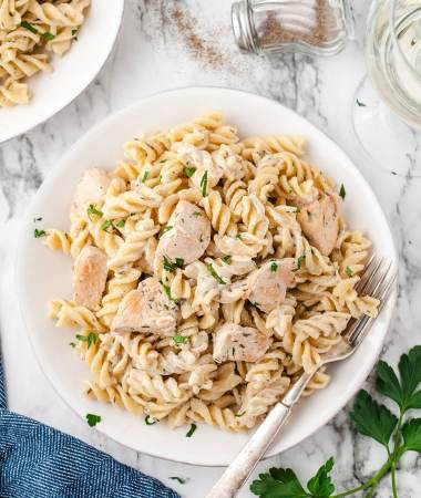chicken and pasta in a white bowl with a fork and a blue towel on the side.