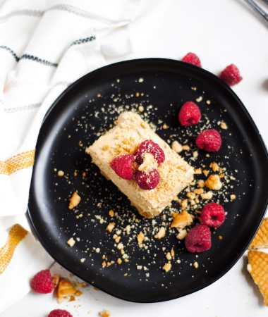a squared slice of no-bake dalgona cheesecake on a black plate with raspberries and crushed cookies on top. A white and yellow towel on the side.