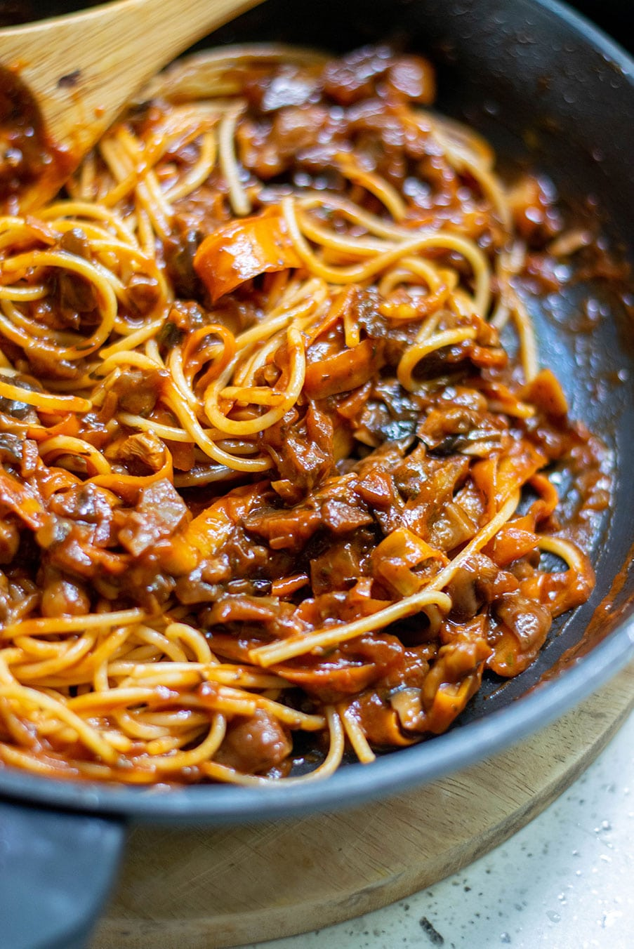 up close shot of spaghetti and mushroom bolognese sauce with a wooden spoon inside a black skillet.