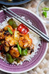 sweet and sour shrimp over white rice in a purple bowl with chop sticks on top.