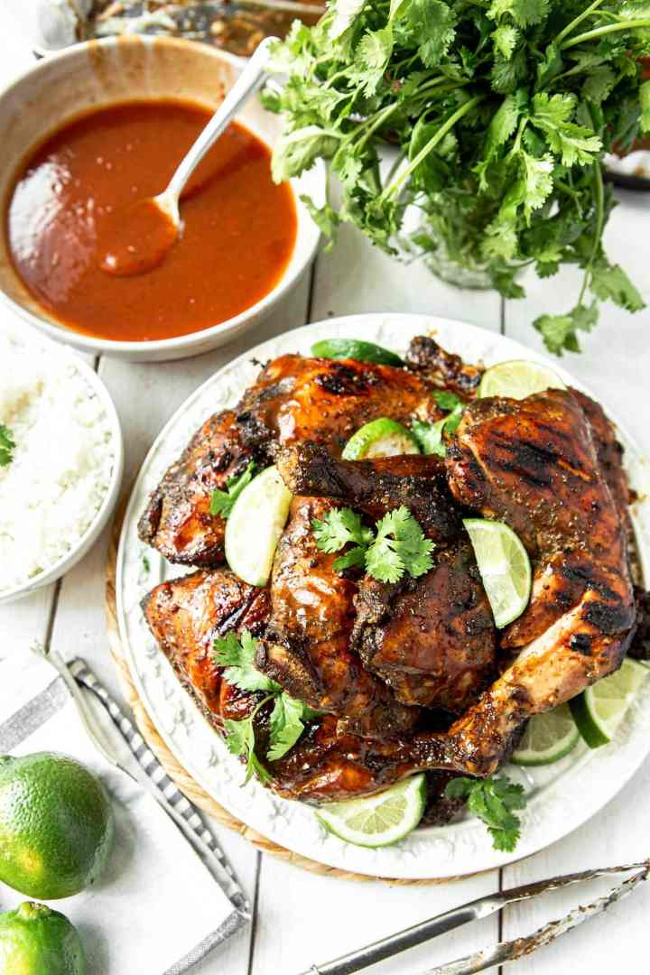Jamaican jerk chicken on a white plate with cilantro and lime wedges. A bowl of red sauce with a spoon and more cilantro and lime on the side.