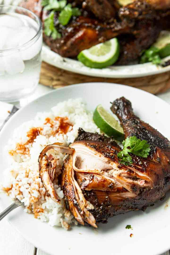 a chicken leg quarter with lime, cilantro, white rice and sauce on top of the rice.