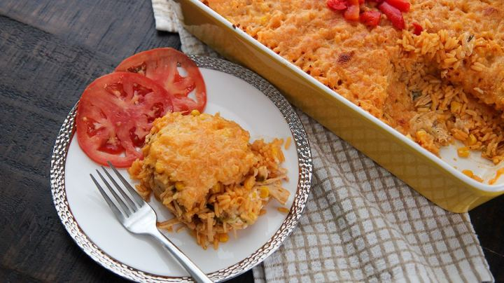 a serving of yellow rice, shredded chicken, cheese, and two tomato slices on a white plate with a fork. A yellow casserole dish in the background.
