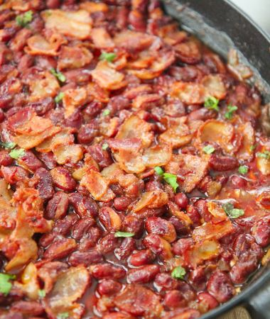 chipotle baked beans in an iron skillet with bacon and parsley on top.