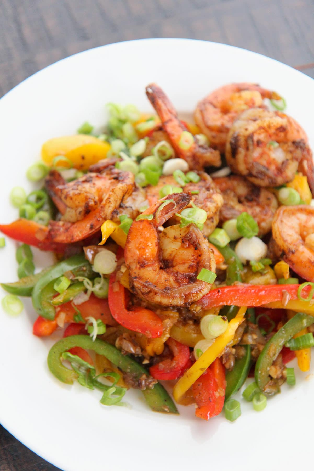 jerk shrimp with peppers and onions on a white plate.