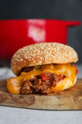 sloppy joe sandwich with cheese up close and a red dutch oven in the background.