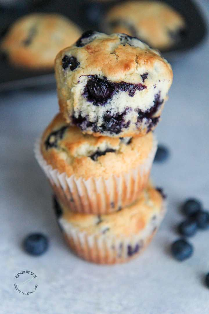 three blueberry muffins stacked with fresh blueberries on the side
