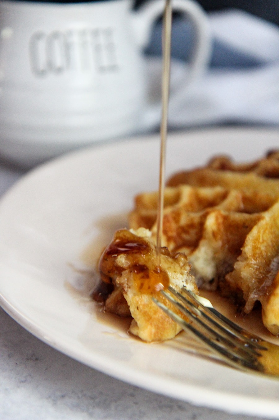 syrup pouring over a piece of waffle with a fork on the side.