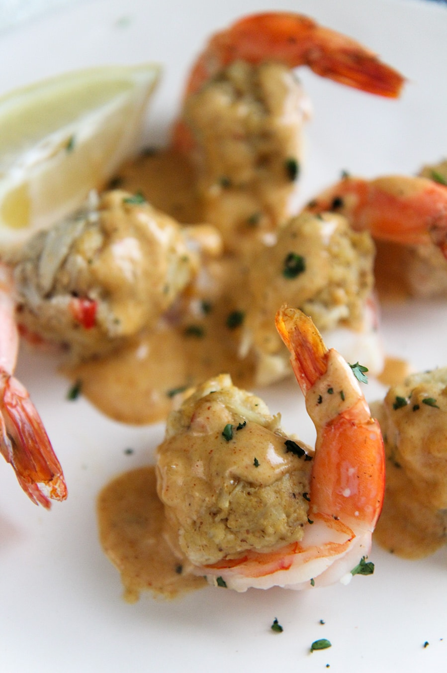 crab stuffed shrimp up close with sauce and a lemon wedge on the side.