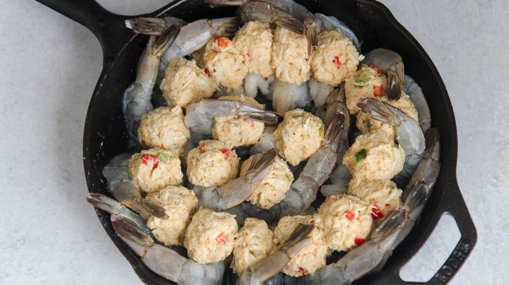 raw shrimp and crab filling in a black cast iron skillet.