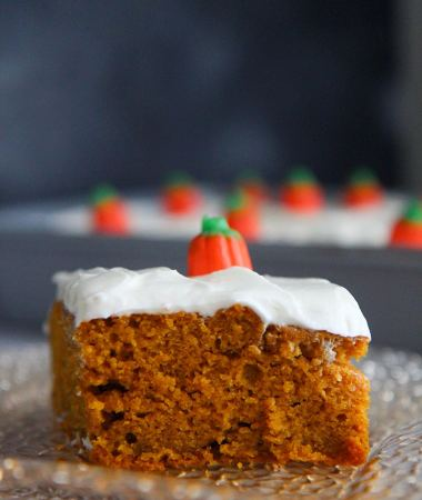 a slice of pumpkin cake with cream cheese frosting up close.