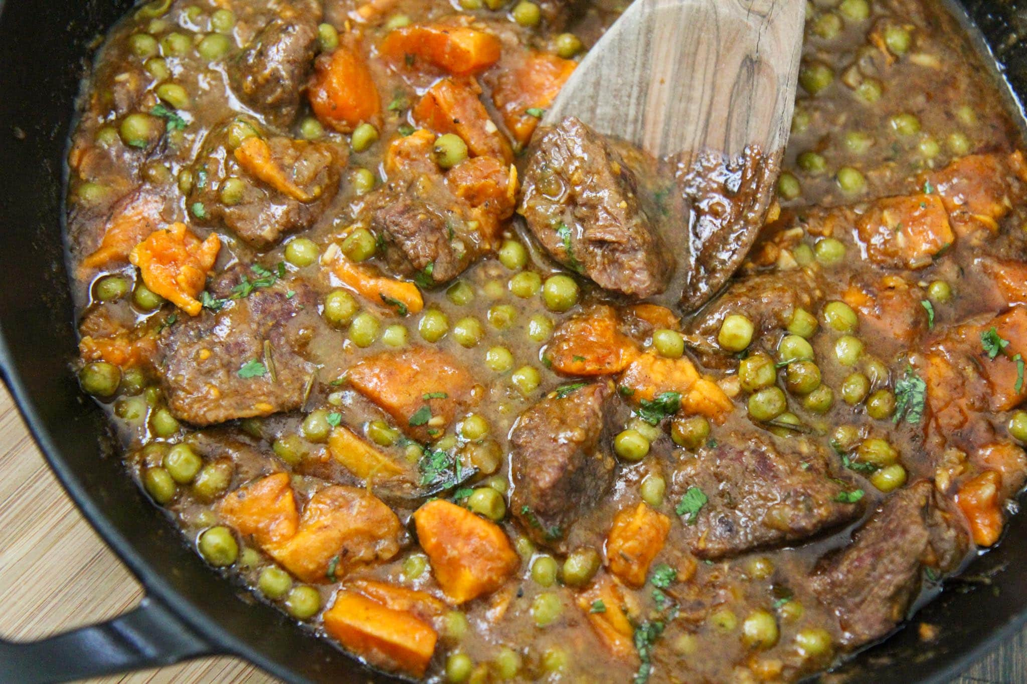 beef and sweet potatoes in a black skillet.