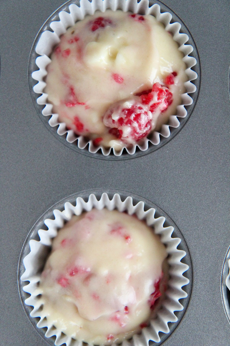 a muffin tin with two cupcake liners filled with batter.