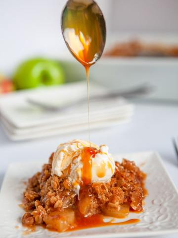 a spoon drizzling caramel sauce over apple crisp with vanilla ice cream on a white plate.