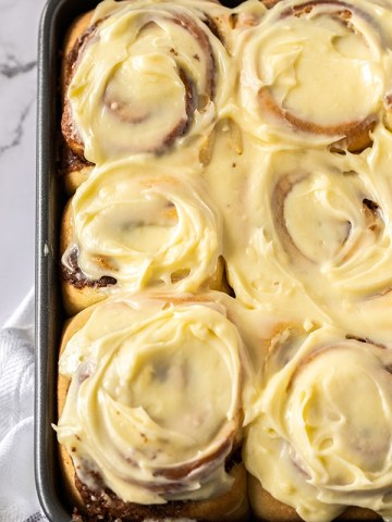 six jumbo cinnamon rolls with cream cheese frosting up close.