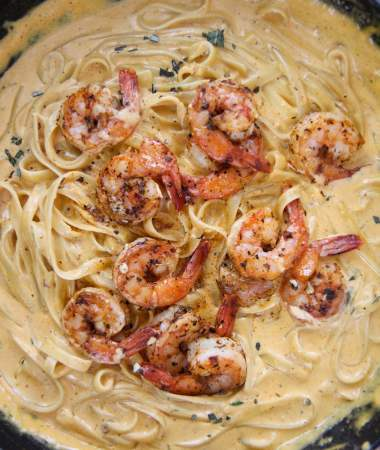 pumpkin fettuccine alfredo with shrimp in a cast iron skillet.