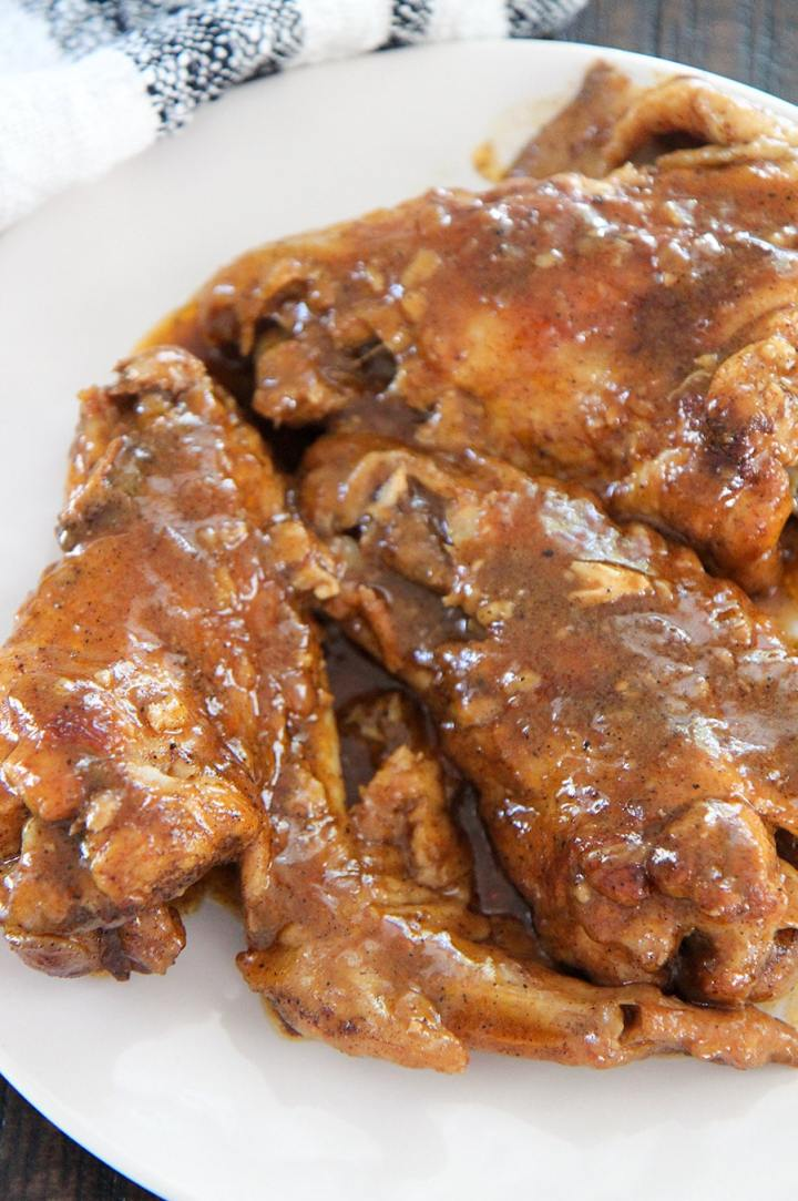 smothered wings on a white plate up close.