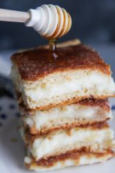 three sopapilla cheesecake bars with drizzled honey on top.
