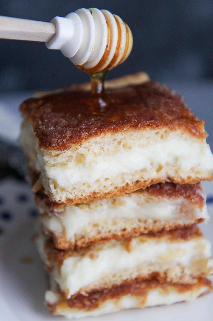 four sopapilla cheesecake bars with drizzled honey on top.