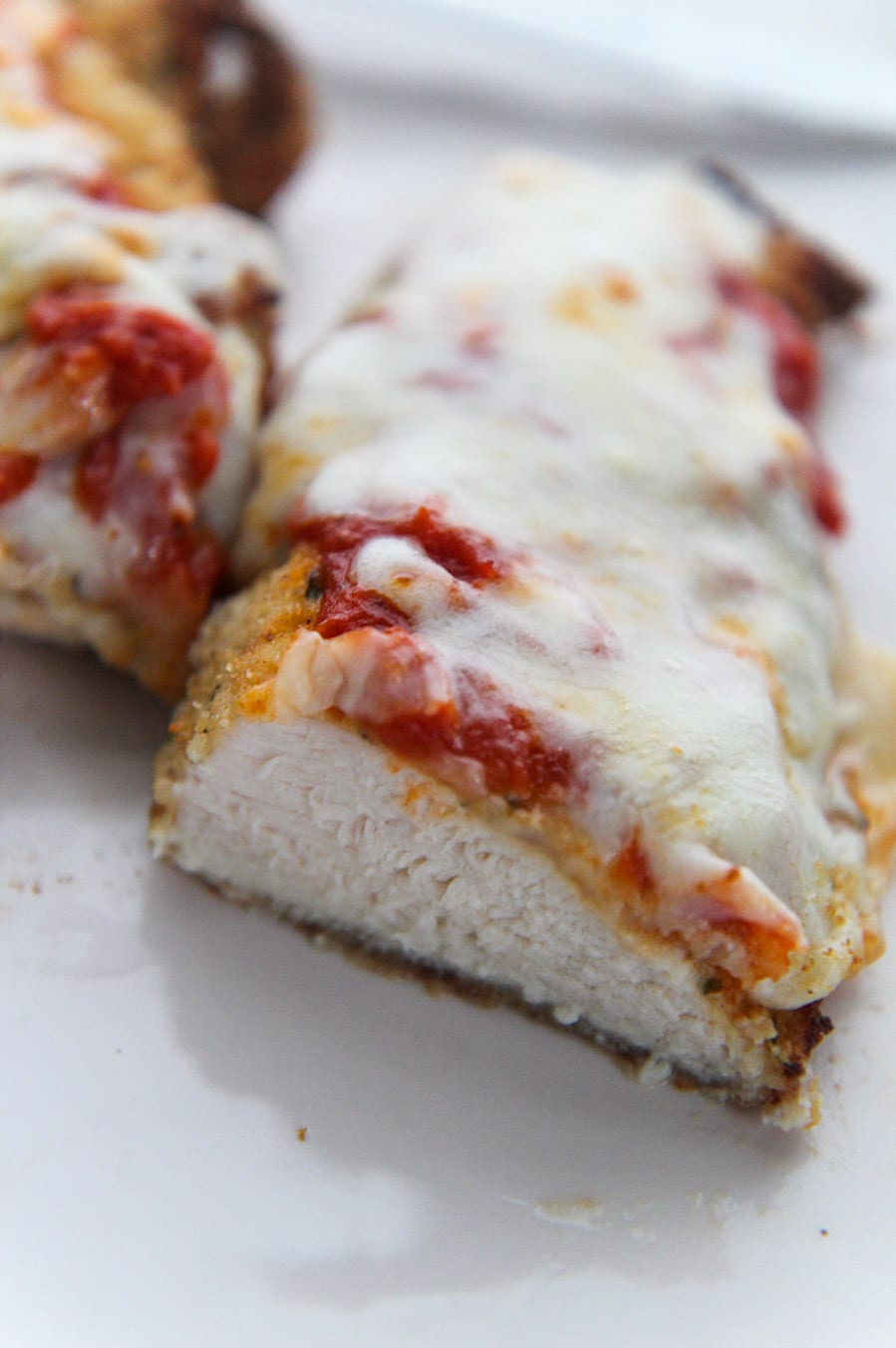 cooked chicken parm sliced in half.