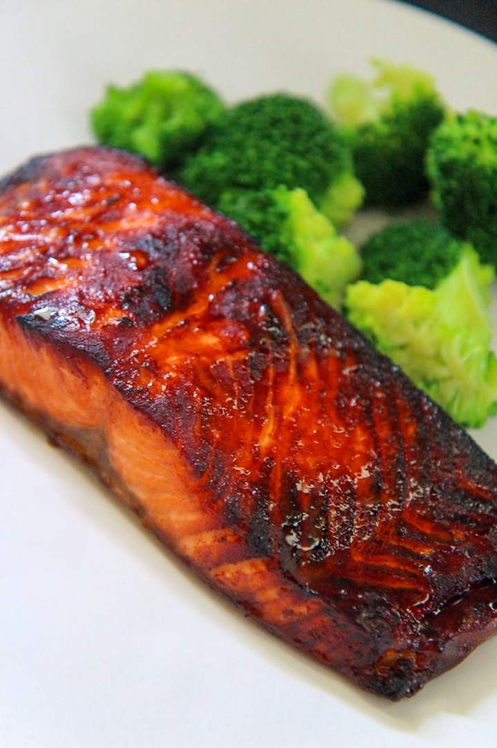 cooked air fryer salmon on a white plate with broccoli