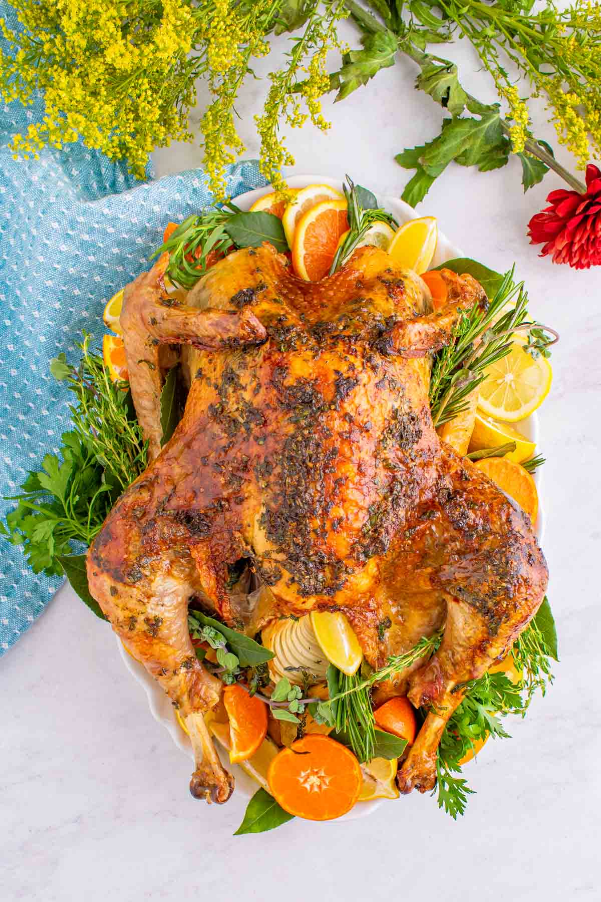 a cooked juicy roast turkey on a platter decorated with orange slices and herbs.
