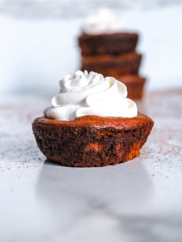 keto mini pumpkin pie up close with whipped cream on top.