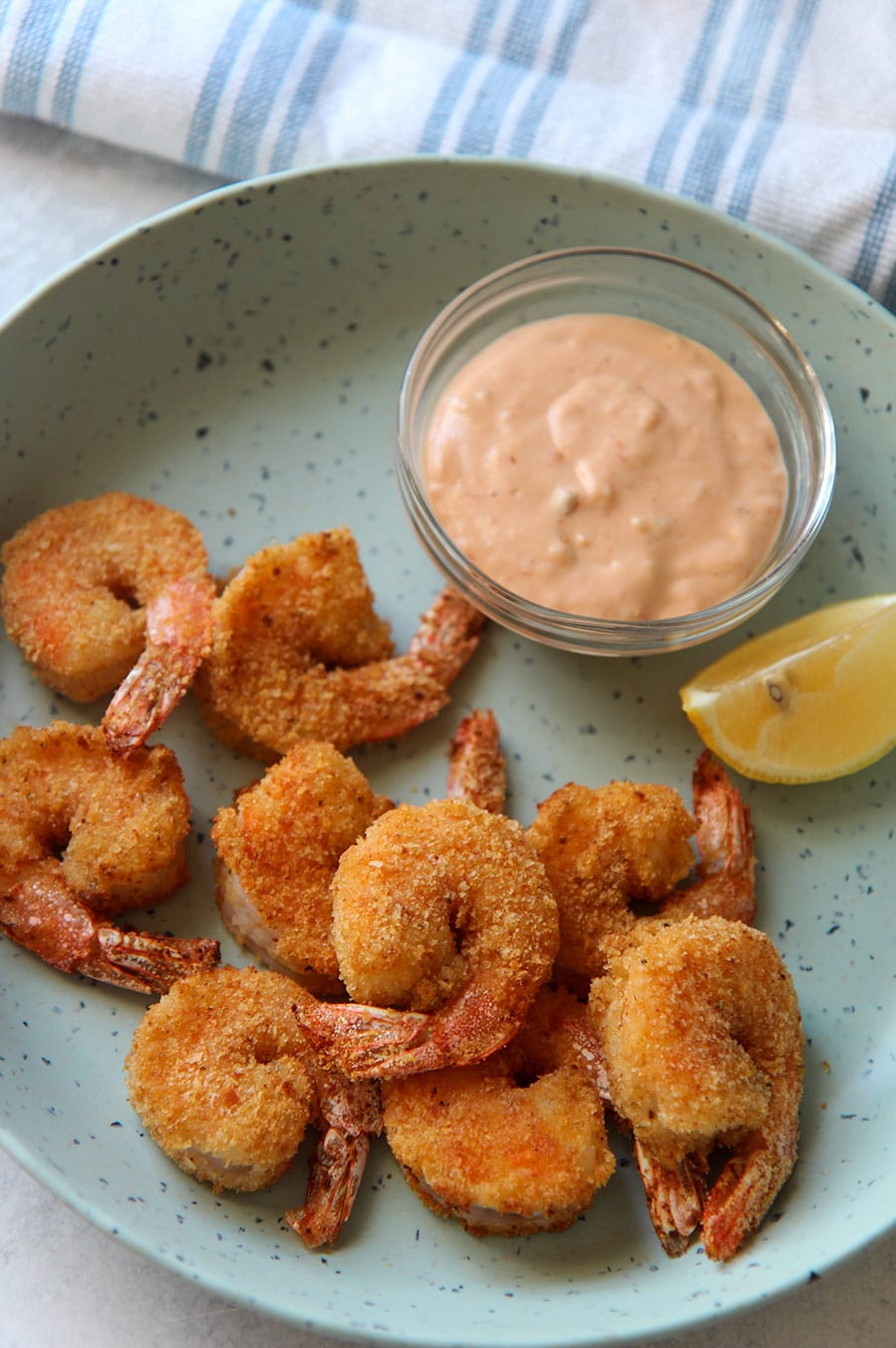 air fried shrimp on a blue plate with a lemon wedge and sauce in a bowl.