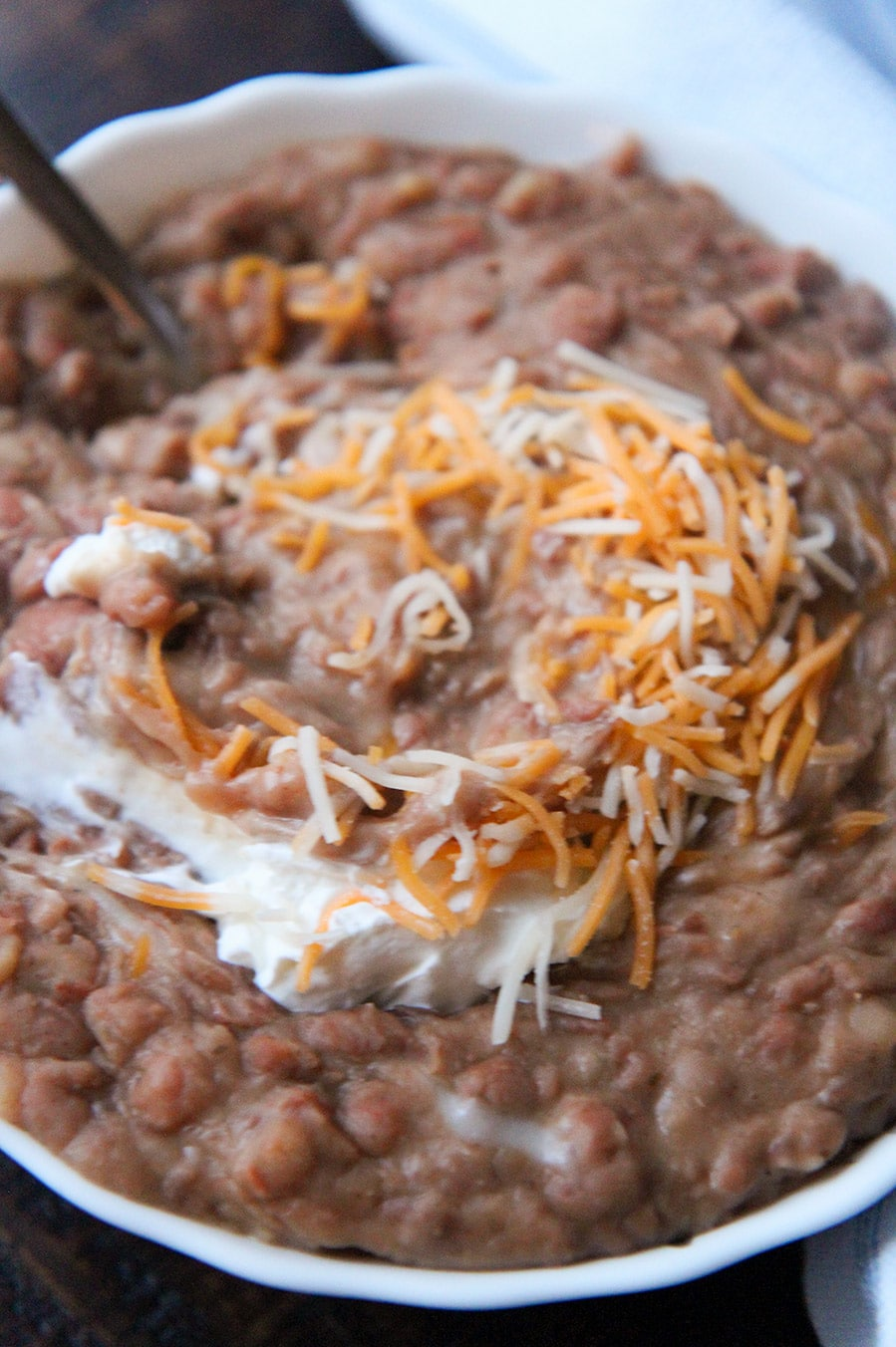 refried beans with sour cream, a spoon, and cheese in a small bowl up close.