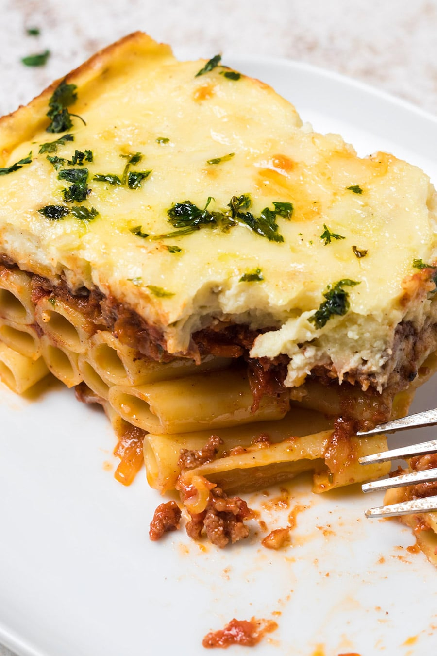 a slice of Greek lasagna on a white plate with a fork on the side.