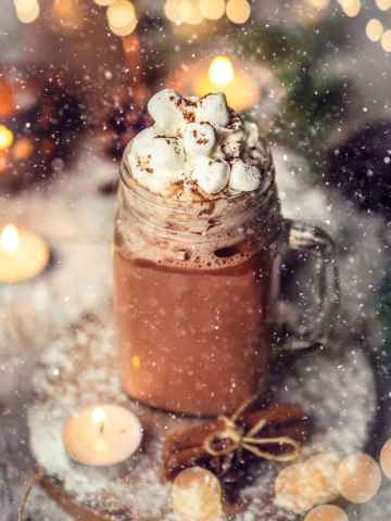 hot chocolate in a glass mug with marshmallows on top.