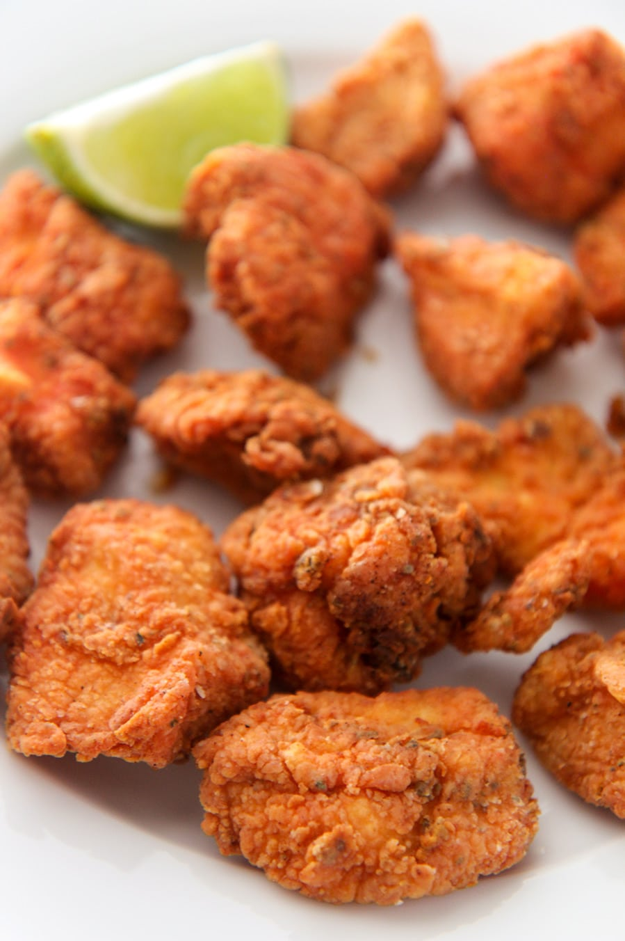 crispy fried chicken bites with a lime wedge up close.