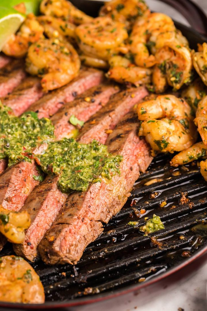 slices of steak with chimichurri on top and shrimp on the side.