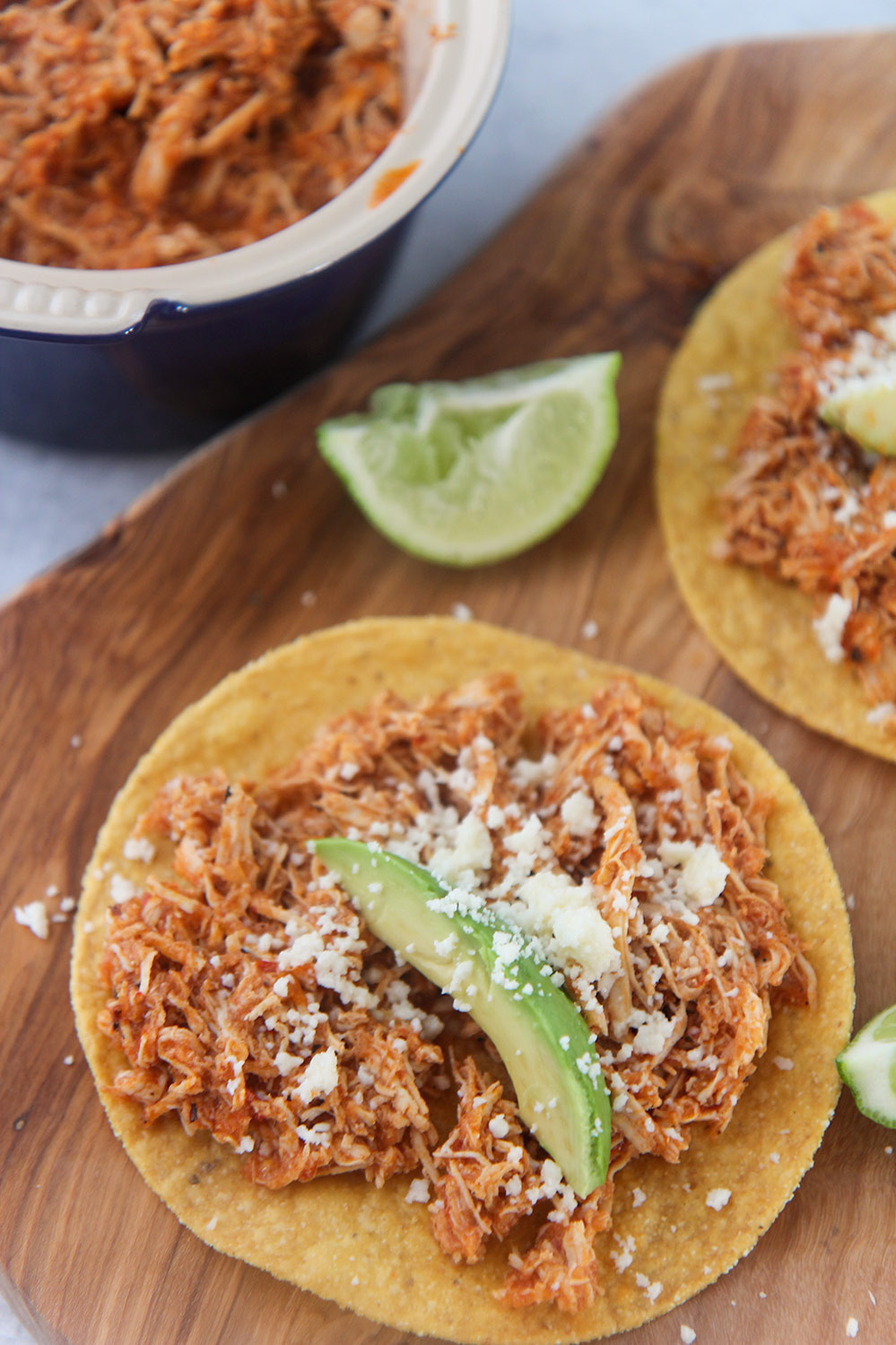 chicken tinga tostadas on a wooden board with lime wedges on the side.