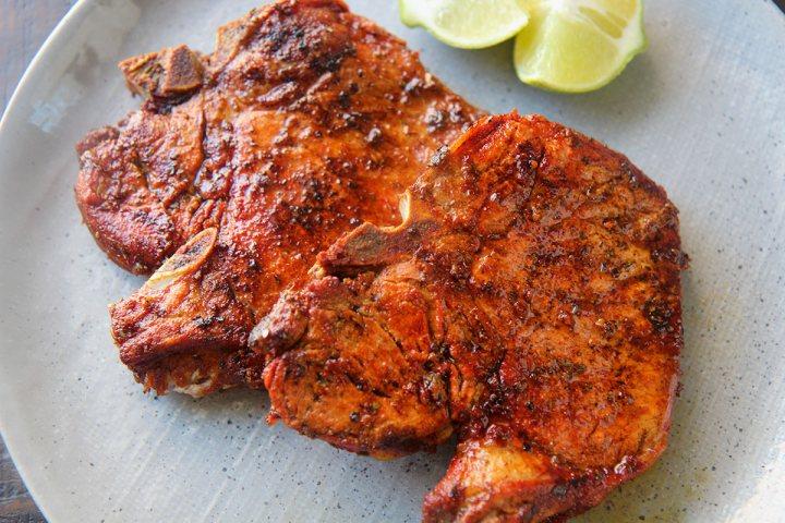 two fried pork chops up close.