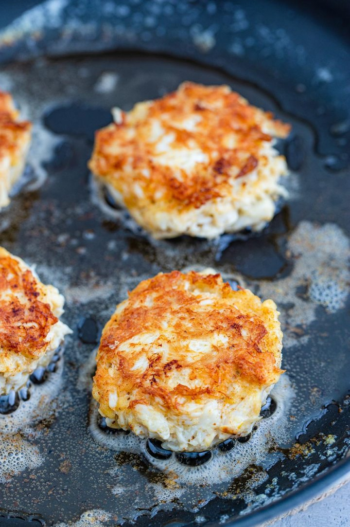 crab cakes frying in a skillet.
