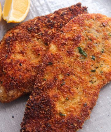 two crispy chicken cutlets with a lemon wedge on the side.