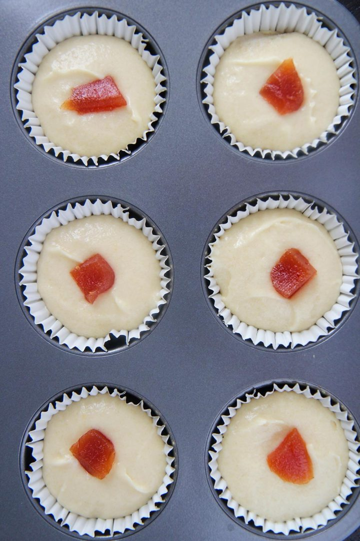 six cupcake liners filled with cupcake batter and guava paste.