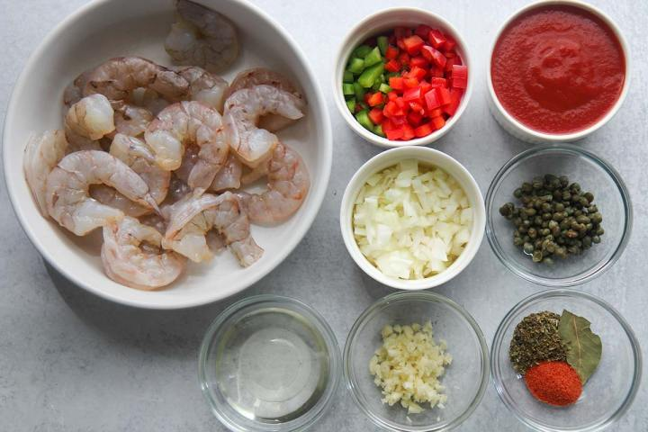 7 small bowls with ingredients and one large bowl with raw shrimp.
