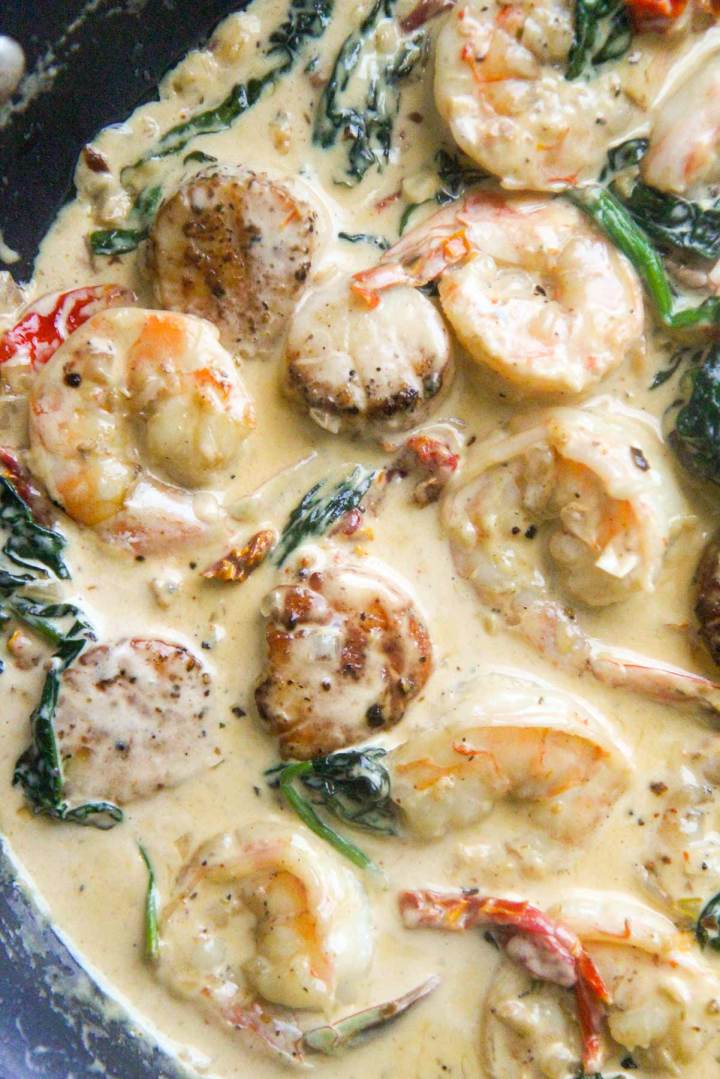 Tuscan shrimp and scallops in a skillet up close.