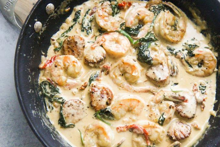 Tuscan shrimp and scallops with fresh spinach in a skillet.
