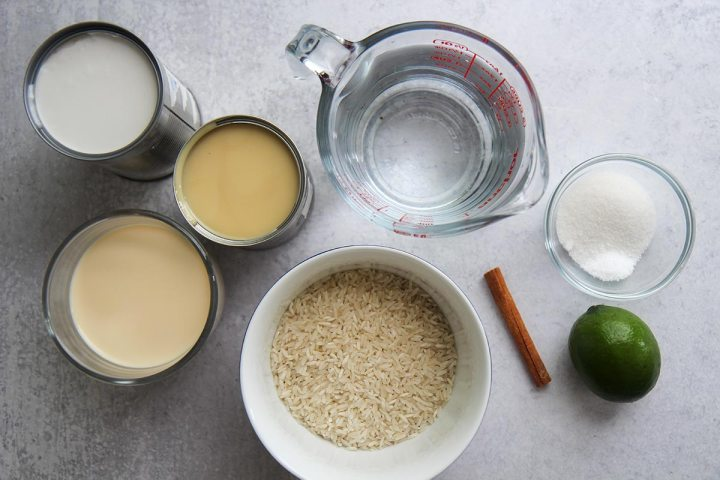 three cans of milk, water, rice in a bowl, a lime, a cinnamon stick, and sugar and salt in a small bowl.