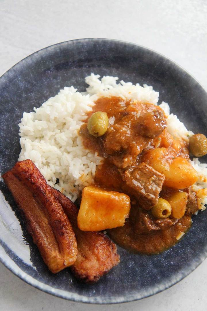 Carne guisada, white rice, and plantains on a plate.