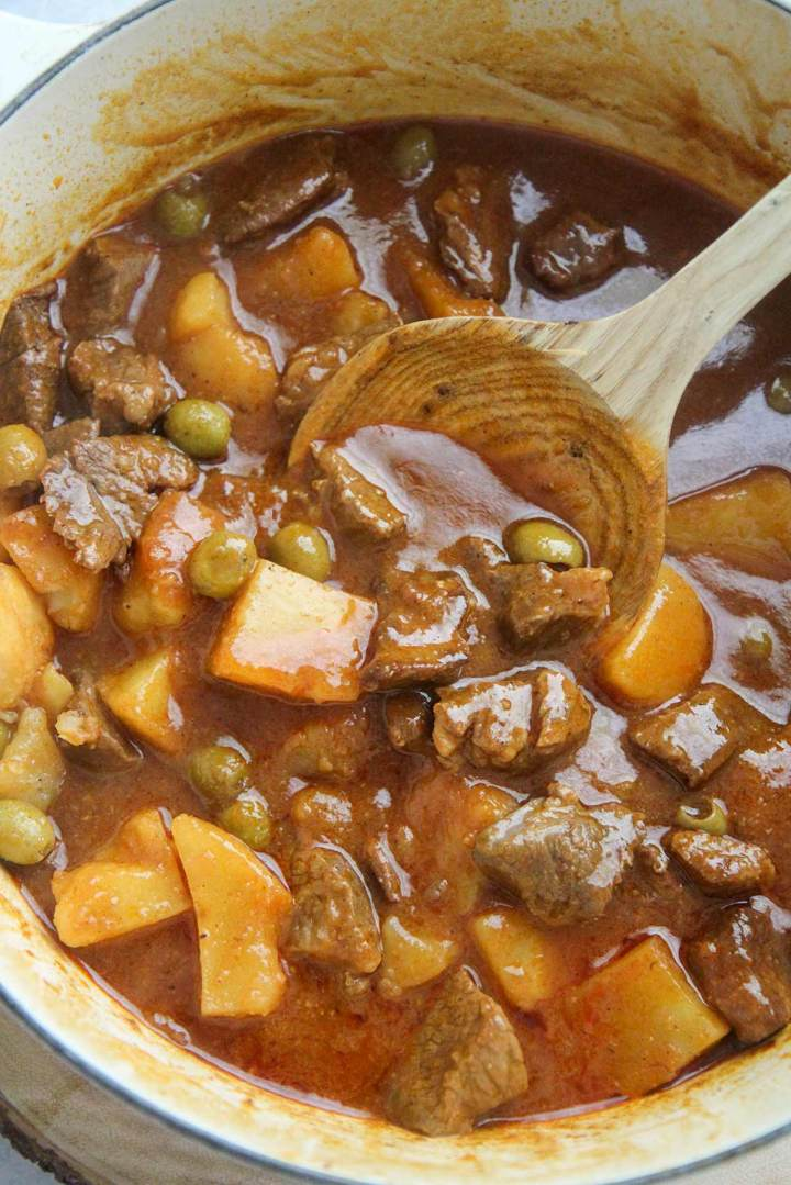 Carne guisada with potatoes and olives in a large pot with a wooden spoon.