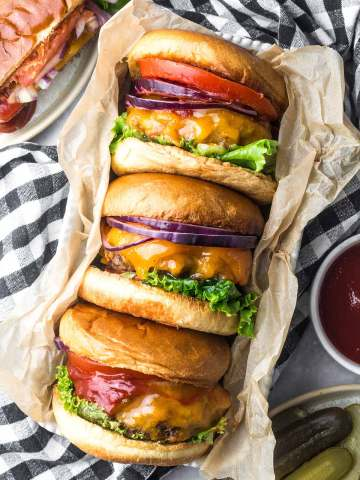 three cheeseburgers with lettuce, tomato, and onions.