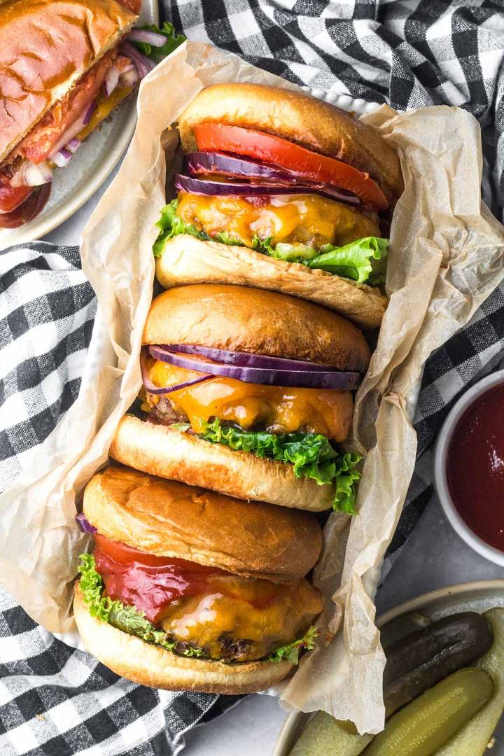 Three cheeseburgers with lettuce, tomato and onion.