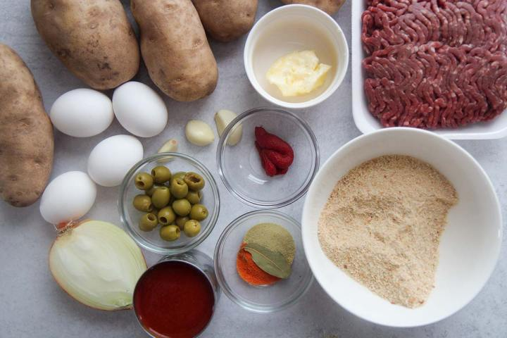 bowls of ingredients including potatoes, ground beef, breadcrumbs, butter, spices, and eggs.