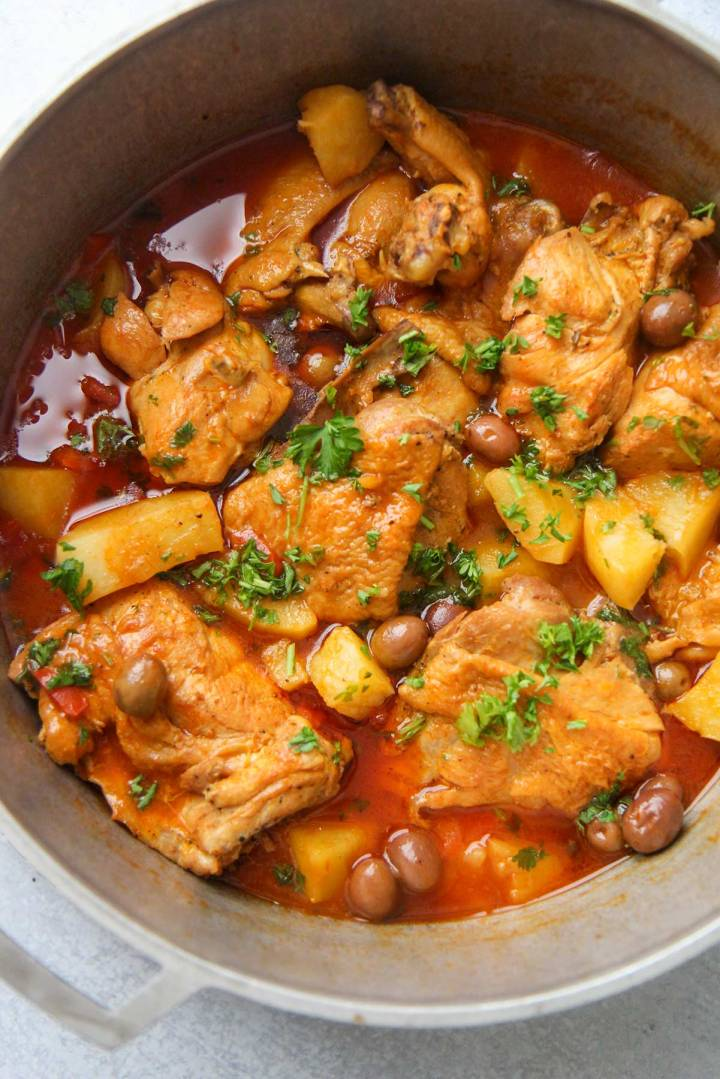 Pollo guisado (chicken stew) in a large pot up close.