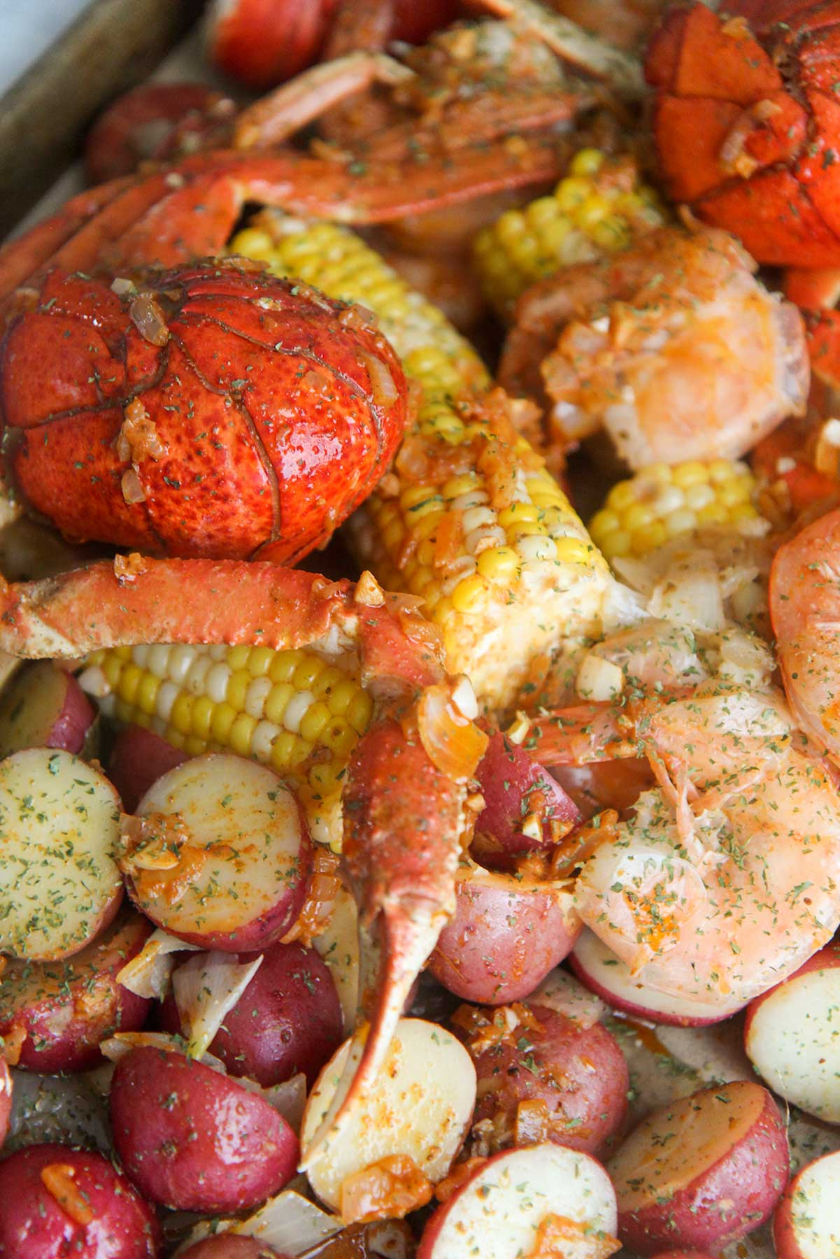 cooked lobster tails, corn, potatoes, sausage, crab legs, and shrimp, with sauce and parsley on top.