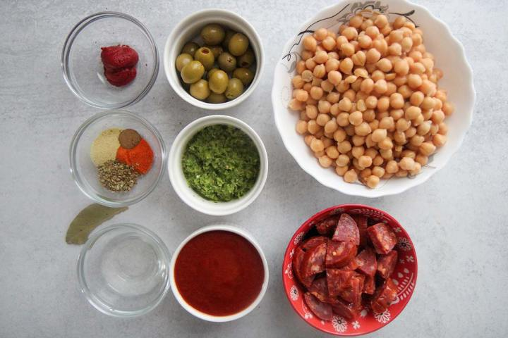 chickpeas, olives, spices, tomato sauce, tomato paste, sofrito, and chorizo in small bowls.